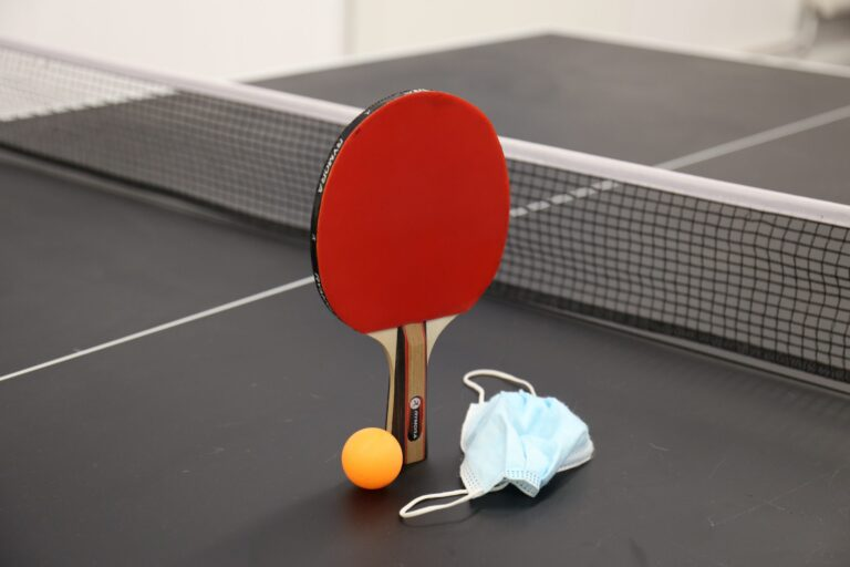 Ping pong bat and ball with face mask laid next to it
