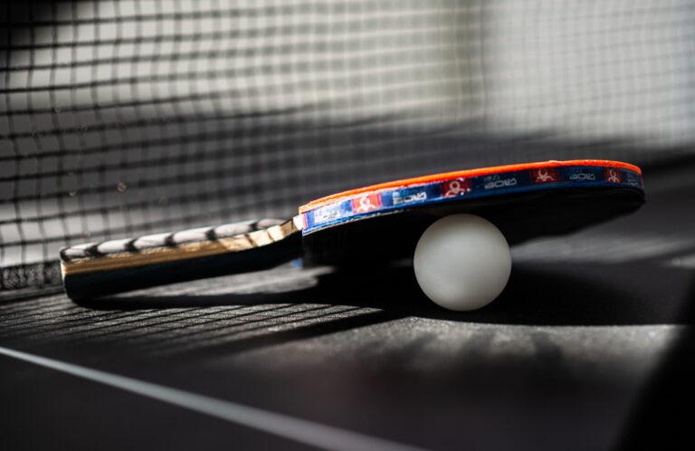 Ping pong bat leant against a ball